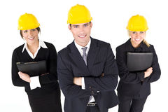 Women In Industry. An industrial concept shot showing 2 women and a man dressed in hard hats. The focus is on the man in the foreground