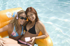 Women On Inflatable Raft In Pool. Portrait of happy female friends listening to music while sitting in an inflatable raft in pool Royalty Free Stock Images