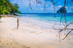 Women inscribed Help on the beach with waves and Rock in the background on a hot sunny day, El Nido, Palawan Stock Image