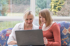 Women are intenly looking into a laptop together Royalty Free Stock Photos