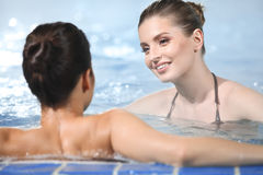 Women in jacuzzi. Young women relaxing in outdoor jacuzzi by the pool royalty free stock photo