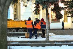 Women janitors in overalls cleaning snow with huge wooden spades on city street. Kyiv, Ukraine - March 24, 2018: Women janitors in overalls cleaning snow with Stock Image