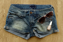 Women jeans shorts, nail polish and sunglasses Royalty Free Stock Photography
