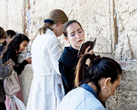 Women at Jerusalem's Western Wall. Several women praying at female side of Jerusalem's Western Wall.  Focus is on the center young woman.  She is twisting from Stock Photo