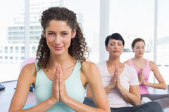 Women with joined hands at fitness studio Stock Image