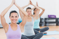 Women with joined hands at fitness studio Stock Photo