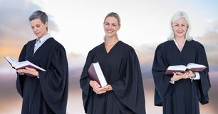 Women Judges holding books in front of sky clouds stock photo