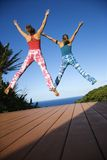 Women jumping into air. Royalty Free Stock Images