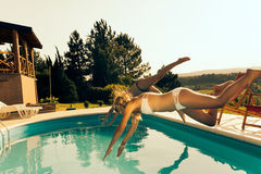 Women jumping into pool Stock Images