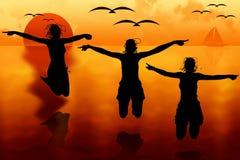 Women jumping at sunset Stock Image
