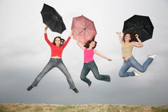 Women jumping with umbre Stock Images