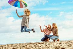 Women jumping with umbrella. Three women full of joy jumping around with colorful umbrella. Female friends having fun outdoor stock image