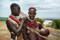 A women of the Karo ethnic group paints the face of a friend
