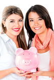 Women keeping savings in a piggybank Royalty Free Stock Image