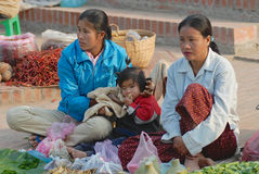 Women with the kid sell vegetables at the food market in Luang Prabang, Laos. Stock Photos