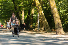 Women with 2 kids in a cargo bike. In the Vondelpark in Amsterdam stock photography