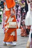 Women in kimono. Young Japanese women in orange kimono with a floral print holding a gold handbag royalty free stock photo