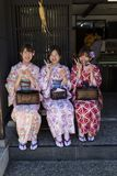 Women in kimono eating a snack in the historical Higashi Chaya Distric Royalty Free Stock Images