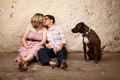 Women Kissing with Dog Nearby. Lesbian kissing couple on floor with pet dog watching Royalty Free Stock Images