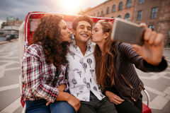 Women kissing man and taking selfie on tricycle. Women kissing men and taking selfie on tricycle. Group of friends having fun on holidays Royalty Free Stock Photography