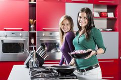 Women in the kitchen. Cute young women in the kitchen Royalty Free Stock Image