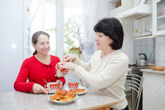 Women  at   kitchen table with   cup of tea. Two mature women talking over coffee in   kitchen Stock Photo