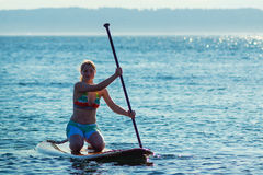 Women Kneeling on Paddle Board Royalty Free Stock Photos