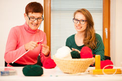 Women knitting with red wool. Eldery woman transfering her knowl Royalty Free Stock Images