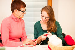 Women knitting with red wool. Eldery woman transfering her knowl Stock Photo