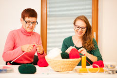 Women knitting with red wool. Eldery woman transfering her knowl Royalty Free Stock Photography