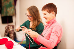 Women knitting with red wool. Eldery woman transfering her knowl Royalty Free Stock Image
