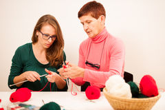 Women knitting with red wool. Eldery woman transfering her knowl Royalty Free Stock Photos