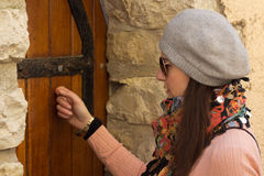 Women Knocking On An Old Wooden Door Stock Photo