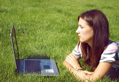 Women with laptop. Young beautiful woman, lying on the grass with the laptop Royalty Free Stock Image