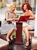 Women at laptop drinking cocktail in a cafe. Stock Photography