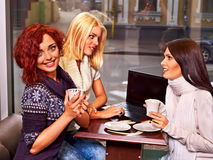 Women at laptop drinking cocktail in a cafe. Royalty Free Stock Photography
