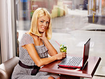 Women at laptop drinking cocktail in a cafe. Royalty Free Stock Images
