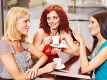 Women at laptop drinking coffee in a cafe. Royalty Free Stock Image