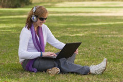 Women with laptop and earphones. Woman with notebook and earphones sitting on the gras royalty free stock photography