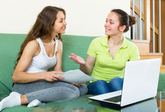 Women with laptop in home interior. Two girls looking financial documents with laptop in home interior Royalty Free Stock Photography