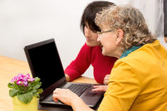 2 Women with a laptop. Two women sitting on a table looking at a laptop Royalty Free Stock Images