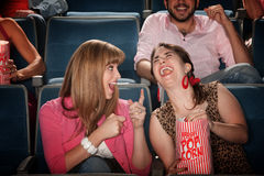 Women Laugh in a Theater. Two pretty young women in the audience laugh together Stock Photo