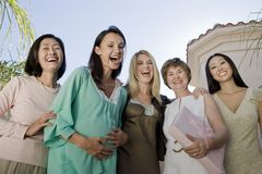 Women Laughing At Baby Shower. Portrait of pregnant women and female friends laughing together royalty free stock images