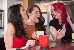 Women Laughing with Cellphone. Three young stylish women at coffee bar looking and laughing at images on cellphone royalty free stock photos