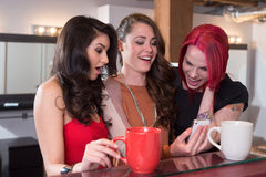 Women Laughing with Cellphone. Three young stylish women at coffee bar looking and laughing at images on cellphone royalty free stock photography