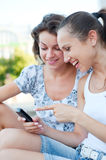 Women laughing and looking at cellphone Royalty Free Stock Photos
