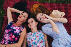 Women lay on grass during picnic in the countryside - Three girls on vacation Stock Photo
