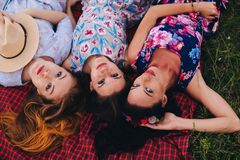 Women lay on grass during picnic in the countryside - Three girls on vacation Royalty Free Stock Image