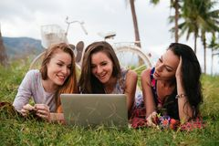 Women lay on grass using laptop together during picnic in the countryside Royalty Free Stock Photo