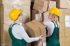 Women laying the boxes. Two hardworking women laying the boxes in factory Stock Images